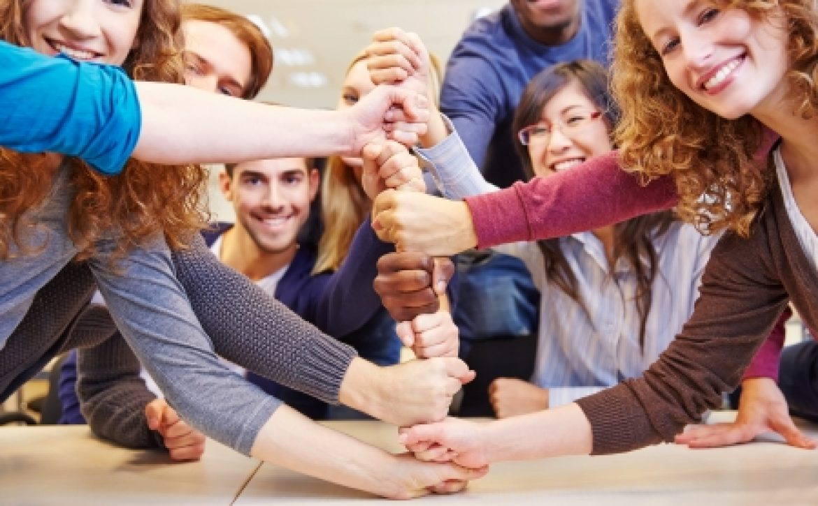 25216283 - students stacking fists for cooperation and teamwork in a university