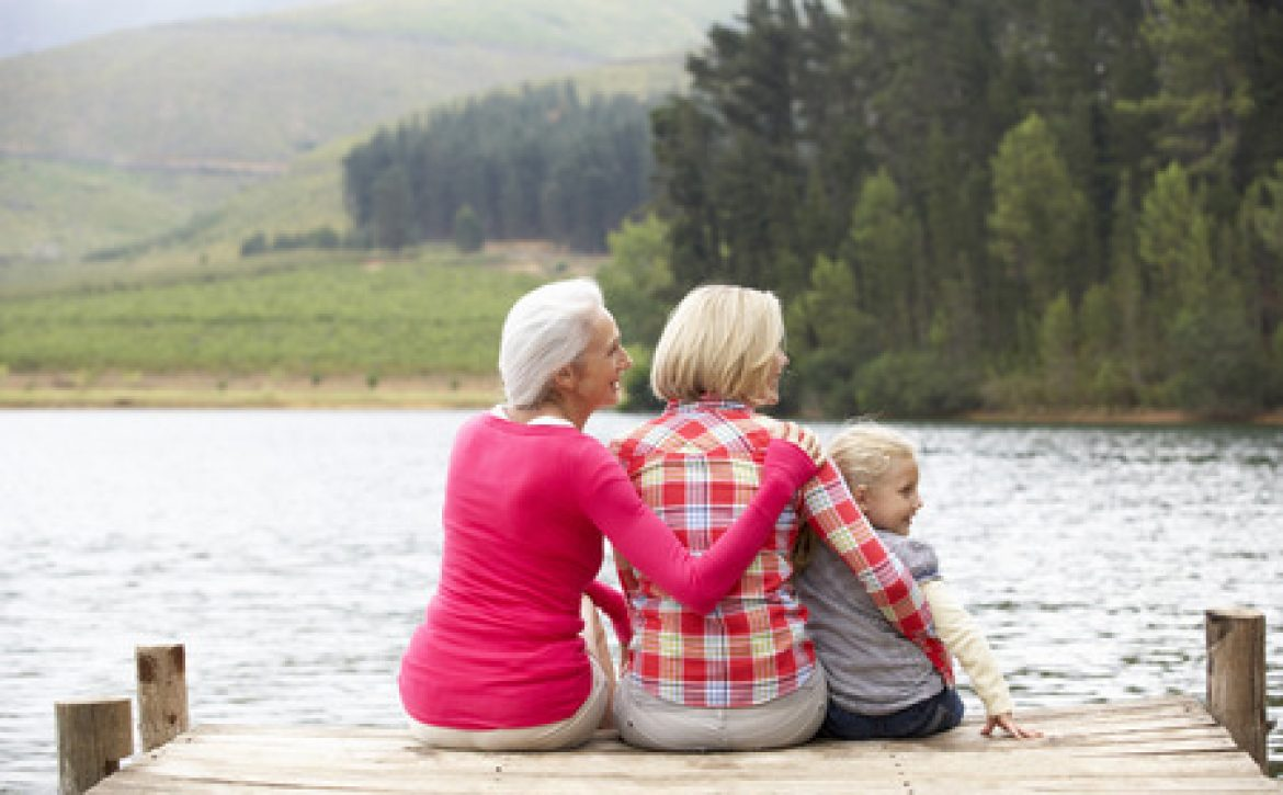 33557701 - mother, daughter and grandmother sitting on a jetty